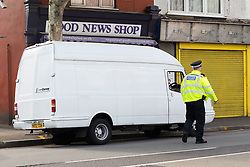© Licensed to London News Pictures. 08/08/2019. London, UK.  A police officer walks past the van at the scene in Leyton this morning in Leyton High Road, where a police officer has been left in a critical condition after being stabbed repeatedly whilst attempting to stop a van in east London. The injured Police Officer, believed to be aged in his thirties, was rushed to hospital and is in a critical but stable condition..  Photo credit: Vickie Flores/LNP