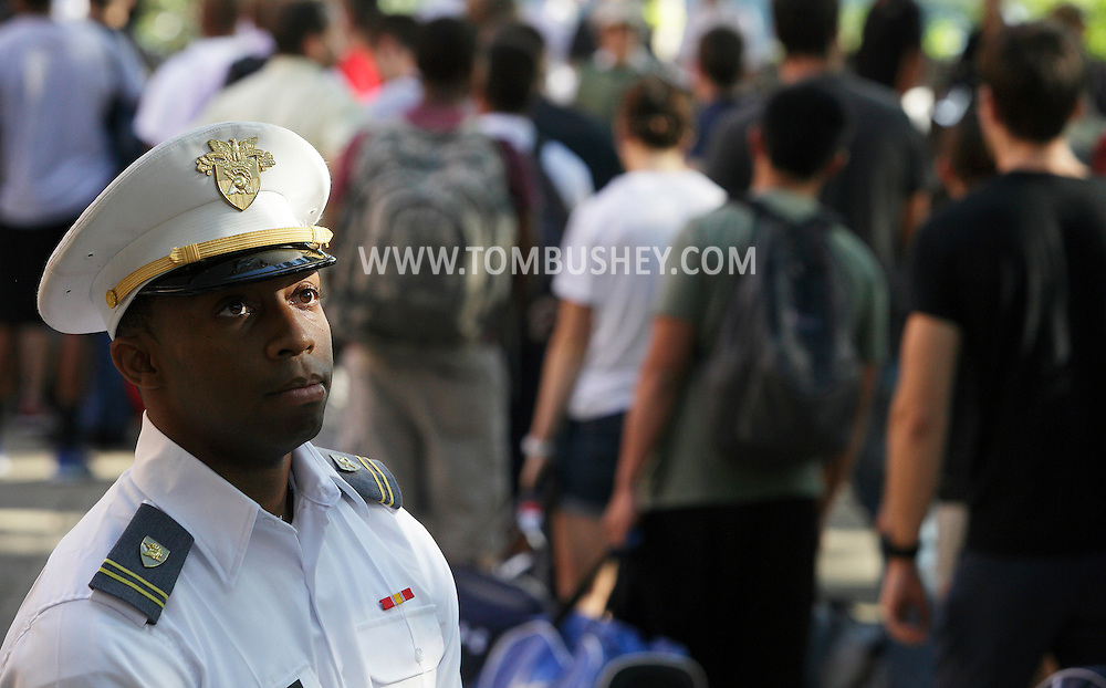 U.S. Military Academy cadet Alfred Fields watches new cadets and their families as they line up outside of Eisenhower Hall at the start of Reception Day at West Point on Monday, July 2, 2012. About 1,150 cadet candidates arrived for Reception Day for the Class of 2016.
