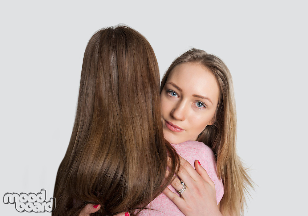 Portrait of girl embracing friend against white background