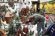 Matthew Busse, 8 watches as Brian Busse of Alexandria, Kentucky put a train on the Huntington Holiday Train display as setup nears completion at the main branch of the Columbus Metropolitan Library in downtown Columbus, Sunday, November 25, 2012..The trains are setup by Applied Imagination on Saturday and Sunday and will run through mid-January.