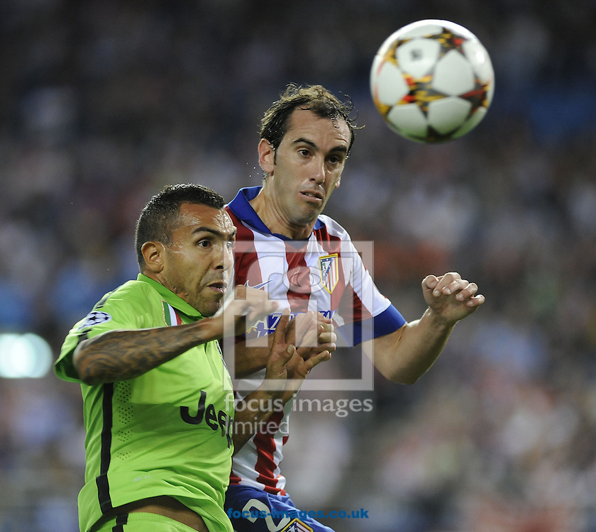 Diego Godin of Atletico Madrid and Carlos Tevez of Juventus during the UEFA Champions League match at Vicente Calder&oacute;n Stadium, Madrid<br /> Picture by Stefano Gnech/Focus Images Ltd +39 333 1641678<br /> 01/10/2014