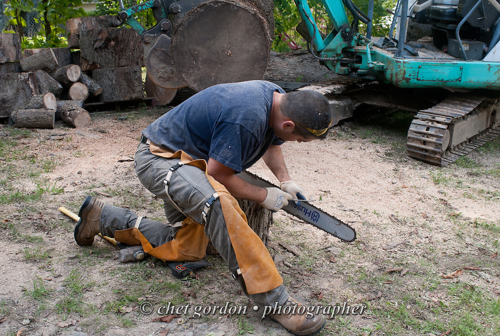 A man sharpens a chainsaw blade during a break while cutting downed logs for firewood in the yard of a private home in Greenwood Lake, NY on Saturday, September 20, 2014.  © Chet Gordon/THE IMAGE WORKS