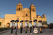 A Mexican mariachi band dressed in traditional charro costume pose in front of the Santo Domingo de Guzmán Church November 5, 2013 in Oaxaca, Mexico.