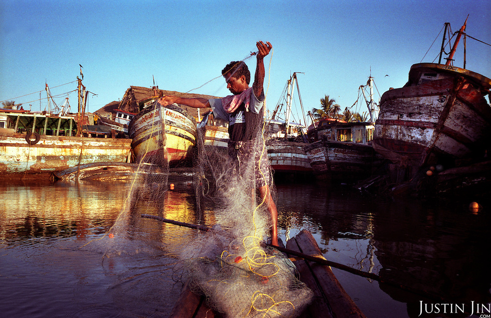 A fisherman ekes out a living in Nagappattinam, in the southeastern coast of India. Behind him are boats smashed by the tsunami. He lost his wife and boat to the waves.  .The December 26, 2004 tsunami killed thousands of people along this coast, smashing boats, roads and houses and tearing thousands of families apart. .Picture taken February 2005 in Nagapptinam, Tamil Nadu, India, by Justin Jin