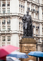 People holding umbrellas walk past the statue of the Duke of Devonshire, Horse Guards Ave, Whitehall, Westminster, London, UK.