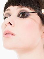 Young Woman Applying mascara close up head shot