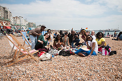 © Licensed to London News Pictures. 31/05/2014. Brighton, UK. Visitors enjoy the afternoon on Brighton beach with a lunch and a glass of wine. The sun is only occasionally making an entrance however that has not stopped the public visiting Brighton with terraces packed and the beach full of people looking for a good time. Photo credit : Hugo Michiels/LNP