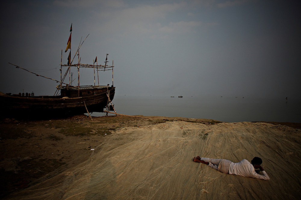 A man is resting on the fishing-nets on the bank of the Meghna river in Betua...This area in the south of Bangladesh has been called ground zero of climate-change due to heavy river and ocean erosion. The lowlying area is also hugely affected by cyclones and rising sea-levels...By the Mouth of Ganges, at the Bay of Bengal is the Island of Bhola. This home of about two million people is considered to be ground zero of climate change. Half the island has disappeared in the past 40 years, and according to scientists the pace is not going to slow down. People pack up and leave as the water get closer. Some to a nearby embankment, while those with enough money move further inland, but for most life move on until the inevitable. It's always about survival for the people in one of the worlds poorest countries...Photo by: Eivind H. Natvig/MOMENT