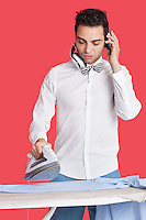 Man ironing cloth while listening music over red background