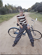 Man leaning against bicycle on dirt road.