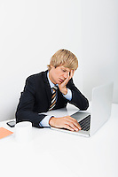 Stressed businessman using laptop at desk in office