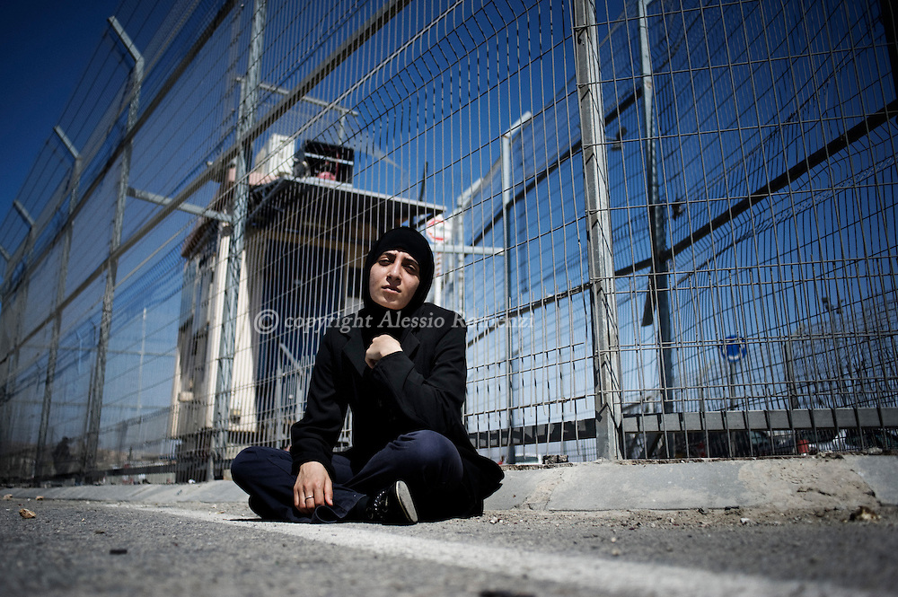 RAMALLAH : A Palestinian woman who identified herself as Neda, from the West Bank city of Bethlehem, sit in defiance within the crossing point of Qalandia at the entrance of Jerusalem on September 17, 2011, in a zone otherwise strictly forbidden for pedestrian. She told reporters that her only wish was to be able to reach Jerusalem.LESSIO ROMENZI