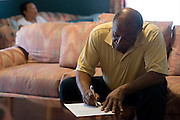 Johnny Lewis fills out a form at his home in Fort Worth, Texas on April 21, 2014. Johnny is the caretaker for Shirley who has been diagnosed with ALS. (Cooper Neill / for AARP)