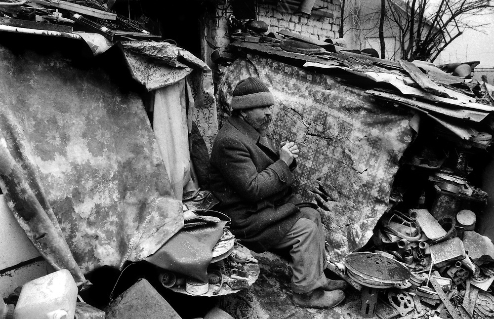 Piljic Niko, 58 year old Catholic Croat.<br /> Praying outside his bombed out home, Ostrovo, Croatia. January 1998