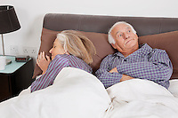 Bored elderly man looking away while spouse sleeping besides in bedroom