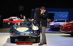 © Licensed to London News Pictures. 08/09/2013. London, England. RM Auctions Classic Car auction at Battersea Evolution, London. Photo credit : Mike King/LNP. RM Auctions 8-9 September 2013 at Battersea Evolution. A man touches a Jaguar D-type.