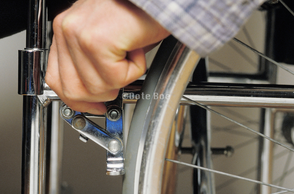 hand putting on the brakes on a wheelchair