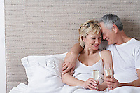 Middle-aged couple drinking champagne in bed