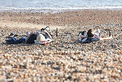 © Licensed to London News Pictures. 12/04/2020. Brighton, UK. Members of the public sunbathe on Brighton seafront at Brighton and Hove, during a pandemic outbreak of the Coronavirus COVID-19 disease.  Photo credit: Liz Pearce/LNP