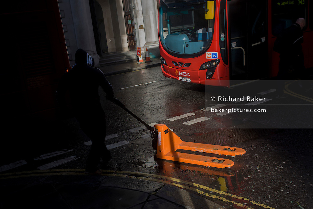 In strong sunlight, a workman waits to cross the road after delivering construction equipment using a hydraulic hand pallet truck in the financial City of London's Threadneedle Street, in front of traffic and still wet after recent showers.