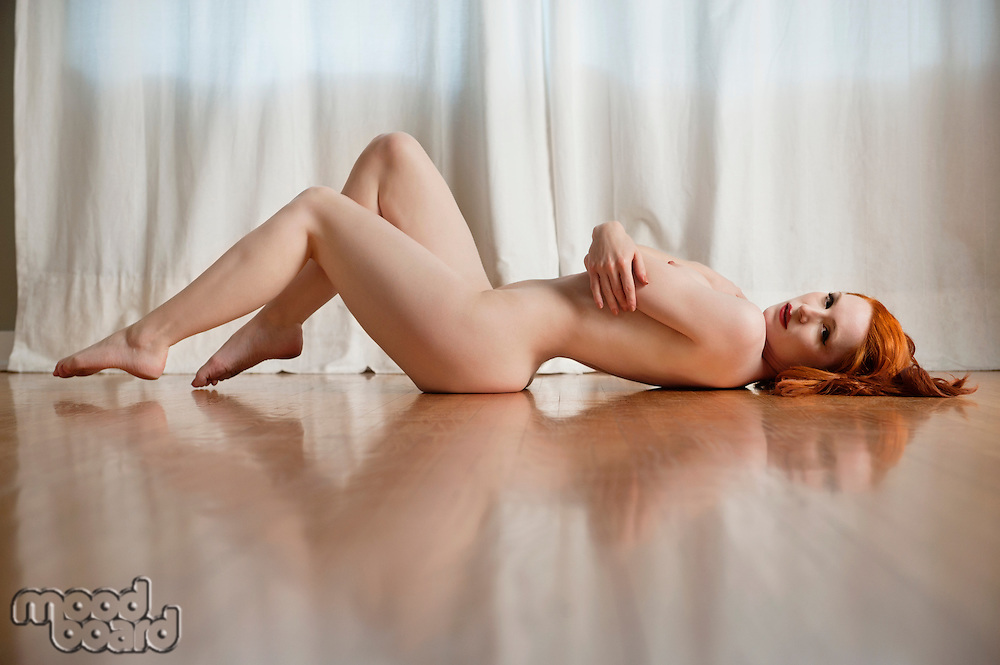 Naked young woman lying on wooden floor at home