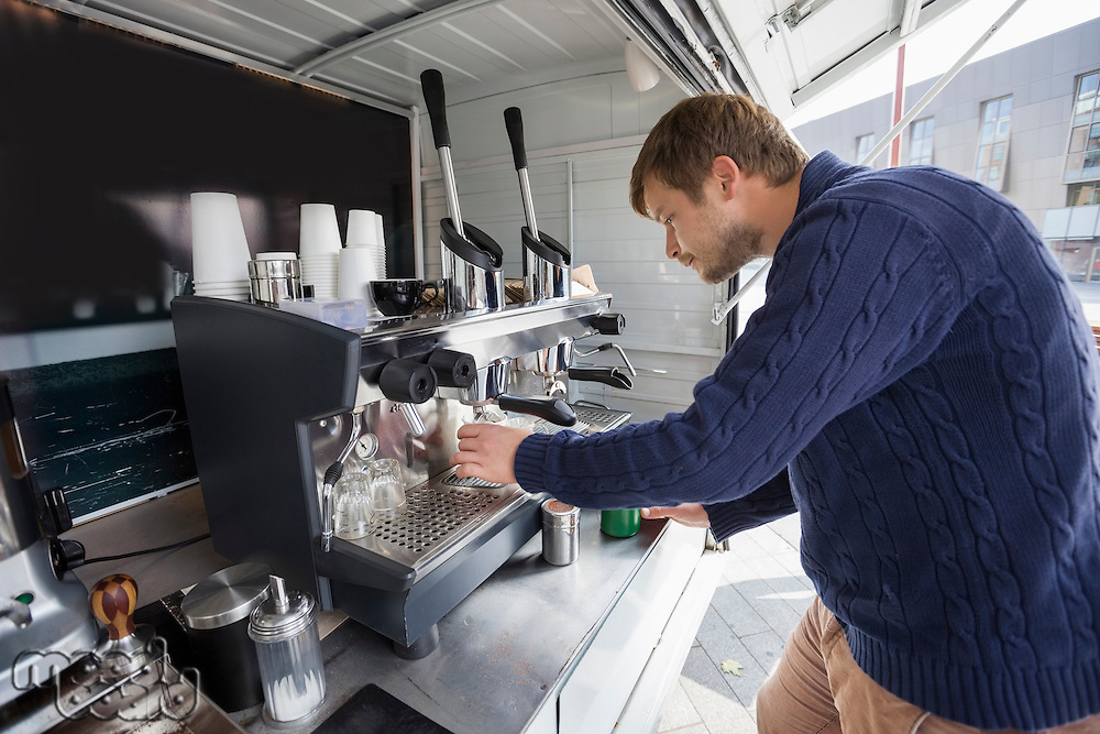 Side view of young man cleaning coffee machine