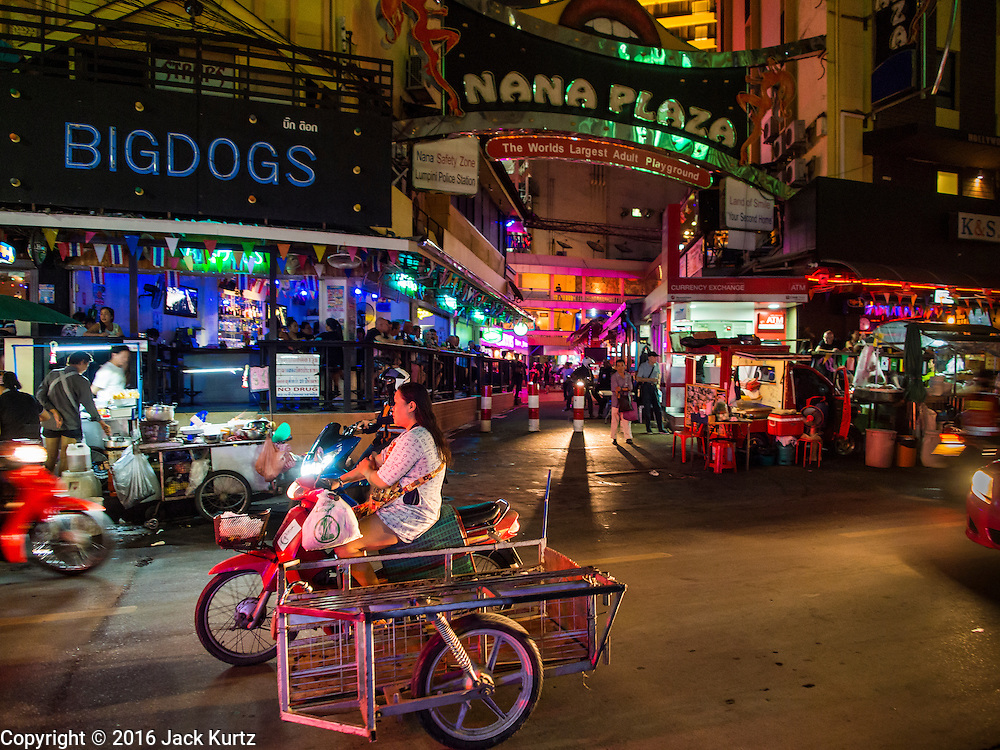 "03 NOVEMBER 2016 - BANGKOK, THAILAND:   Traffic goes past the darkened main entrance to Nana Plaza, one of Bangkok's most famous ""adult entertainment districts."" Bangkok's infamous nightlife has been scaled back during the mourning period for the late Bhumibol Adulyadej, King of Thailand. The revered King died on 13 October 2016 at age 88. The government declared a year of mourning. The government ordered Thailand's notorious adult entertainment districts to turn off their neon lights, dress employees in black and ensure that music can't be heard on the street in front of the venues for 30 days, the government said the entertainment venues could resume normal operations on 14 November.      PHOTO BY JACK KURTZ"