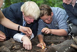© Licensed to London News Pictures. 30/07/2015. London, UK. The Mayor of London and MP for Uxbridge and South Ruislip Boris Johnson pictured trying to light a fire with children at the Wide Horizons Environment Centre in Bexley where he explored their new outdoor learning centre which was built by an 'army of volunteers' on a once derelict site. Photo credit : James Gourley/LNP
