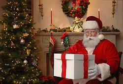Santa next to a Christmas tree giving a gift