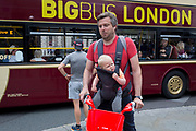 A father cyclist on a rental bike carries his child on a chest harness as a tour bus drives past in Parliament Square, Westminster, on 18th June 2019, in London, England.