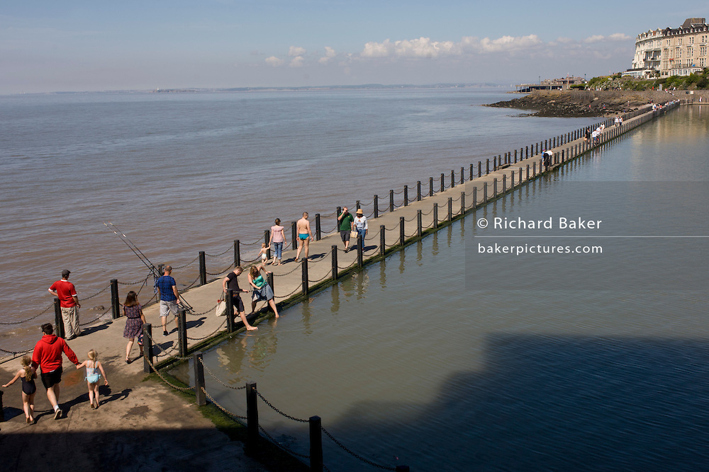 Visitors to Weston-super-Mare walk over the causeway on the seaside resort's seafront.