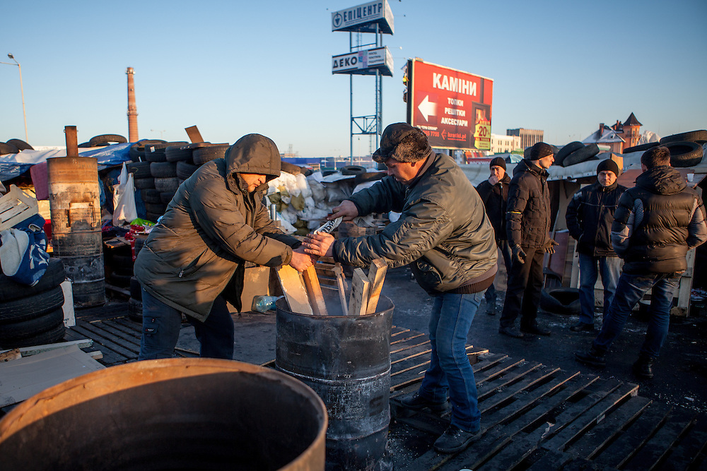 "Activists Dimi (left) and Bosch are preparing a fire for heating at the barrikades blockading a building supplies store named ""Epicenter"" in the city of Lviv, Ukraine. Two people passing by."