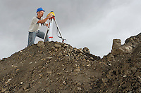 Surveyor using theodolite on site
