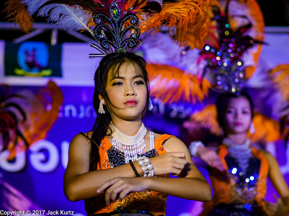 """03 NOVEMBER 2017 - BANGKOK, THAILAND: Entertainers on stage during Loi Krathong at Wat Prayurawongsawat on the Thonburi side of the Chao Phraya River. Loi Krathong is translated as """"to float (Loi) a basket (Krathong)"""", and comes from the tradition of making krathong or buoyant, decorated baskets, which are then floated on a river to make merit. On the night of the full moon of the 12th lunar month (usually November), Thais launch their krathong on a river, canal or a pond, making a wish as they do so. Loi Krathong is also celebrated in other Theravada Buddhist countries like Myanmar, where it is called the Tazaungdaing Festival, and Cambodia, where it is called Bon Om Tuk.     PHOTO BY JACK KURTZ"""