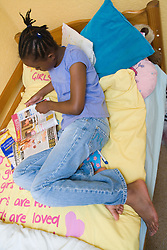 Teenage girl lying on her bed and reading a magazine,
