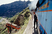 South Orient Express passing a diesel locomotive suspended in the air as a monument for the completion of the tracks through Copper Canyon at Temoris.