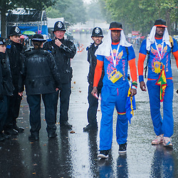 London, UK - 25 August 2014: revellers and police officers under heavy rain during the Notting Hill Carnival in London.