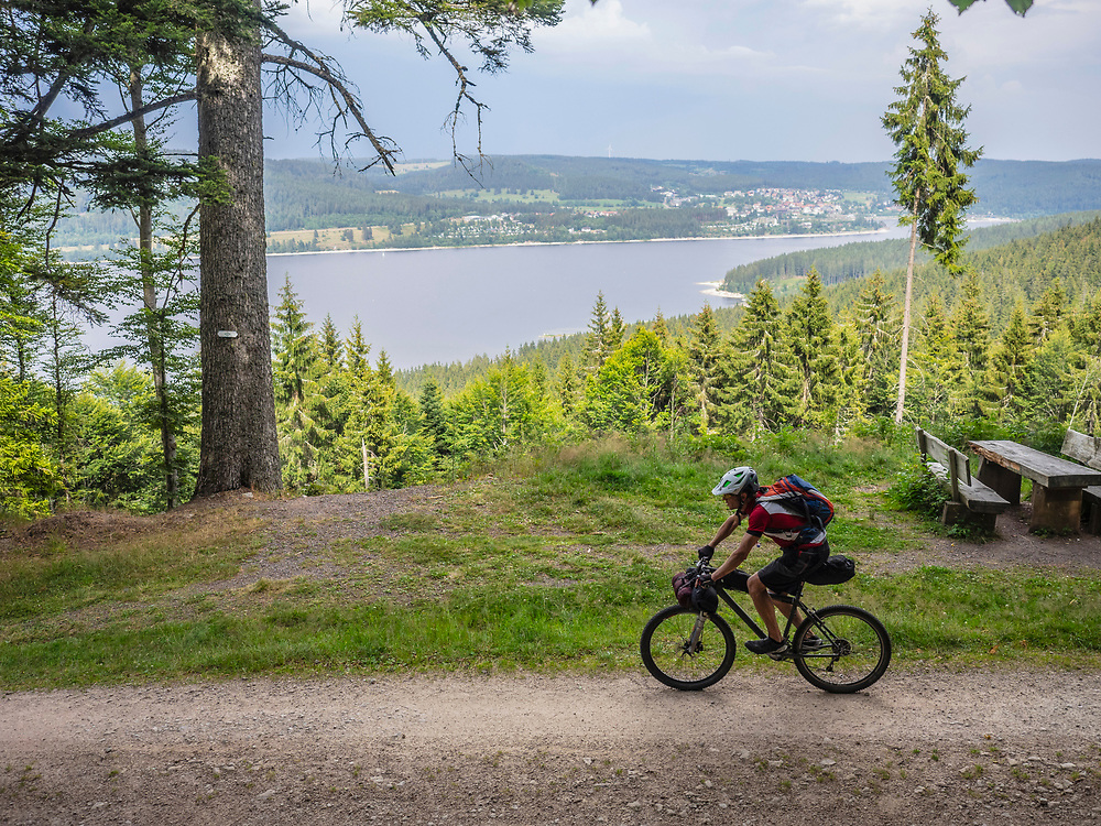 Mountain biker cycling by lake in the background near Schluchsee, Baden-Wuerttemberg, Germany