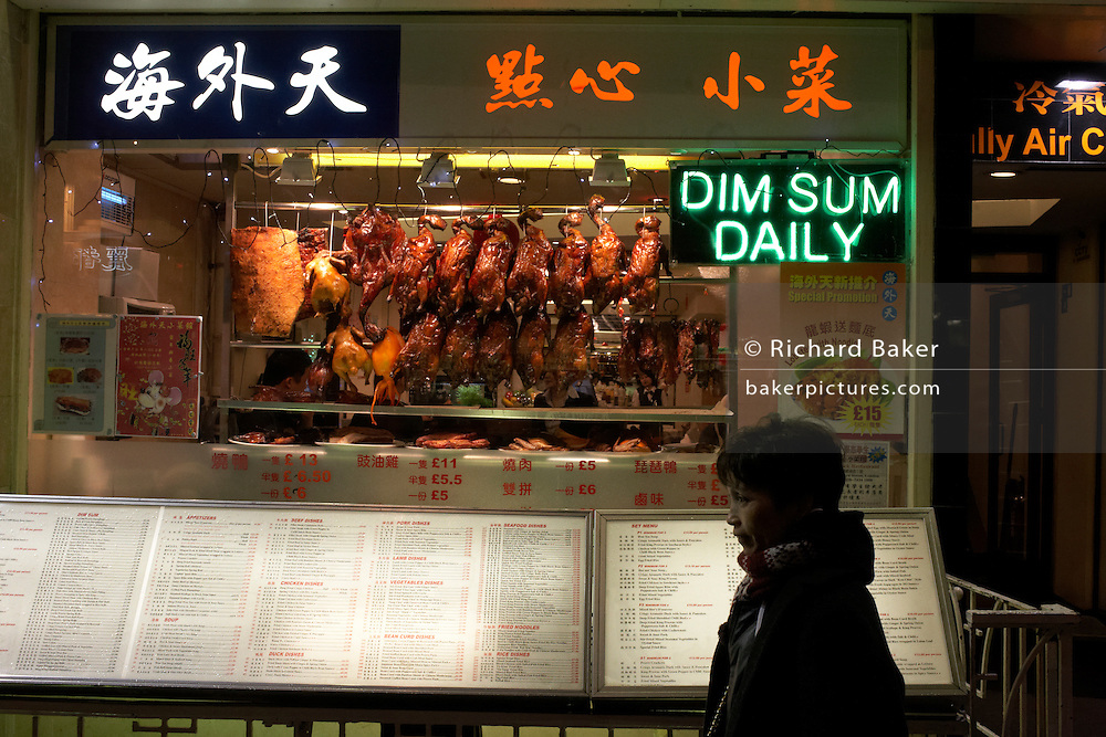 A passer-by stands outside a Chinese Restaurant offering Dim Sum in Chinatown, home to London's ethnic Chinese community.