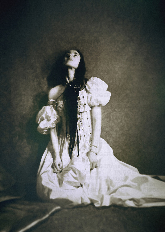 A woman in a white gown and jewelry, with long black hair and miserable facial expression, seated on her knees by a decorated wallpaper.