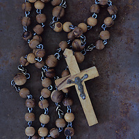 Rosary with crucifix lying on rusty metal sheet