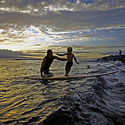 A young surfer gets lessons near Kaanapoli, Maui.  A beautiful sunset throws the final golden light on the ocean.