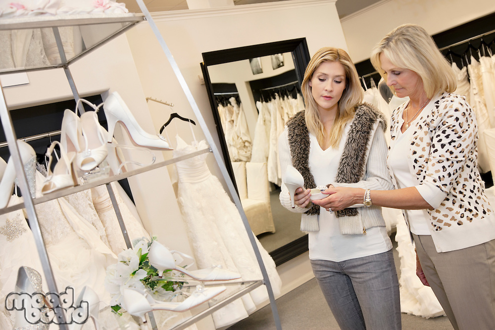 Young woman with senior mother looking at footwear in bridal store