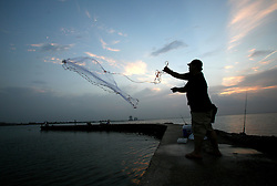 29 August 2006. New Orleans, Louisiana. Lakeview. Lake Pontchartrain. Local fishermen cast their nets and land catfish from the still waters that just 12 months ago devastated the area as they filled back into the city, rupturing the nearby 17th street canal. The connection New Orleans and south Louisiana has with the water is inextricable. The two are forever linked together and until the Army Corps of Engineers is able to build sufficient flood protection, and the greater world is able to control global warming and rising seas, the city and the region will continue to be at increased risk for even greater devastation in the years ahead.<br /> Photo Credit©; Charlie Varley/varleypix.com