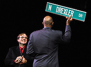 Paul Allen looks on in fondness as Clyde Drexler shows off the new road sign presented to him which will hang on the street beside the Rose Garden. Many fans and former players came out to assist him in retiring his jersey.