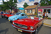 In the arts district 800 block of Main St., Millville, NJ, an antique Ford Mustang, VW and other cars line up in antique car show