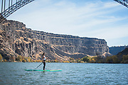 Woman doing yoga on a Stand Up Paddle Boarding under the Perrine Bridge on the Snake River in Twin Falls, Idaho. MR