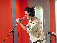 Young woman singing in studio profile