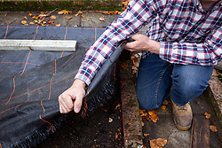 Covering an empty bed in the vegetable garden with black fabric to stop it getting weedy over winter