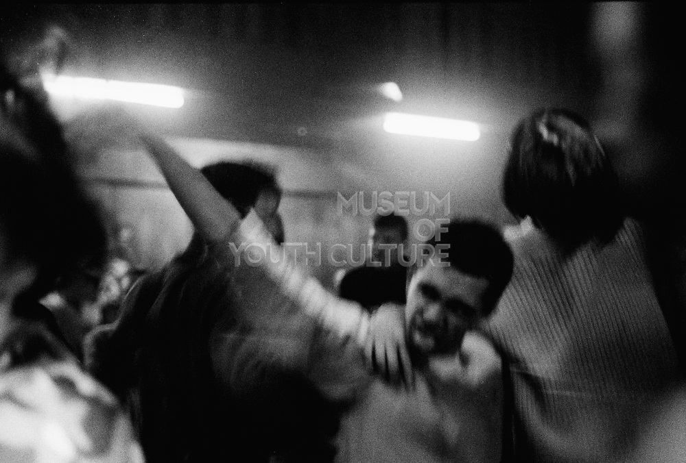 Man with his arm round his friend, sticking his tongue out on the dance floor, Russia, 2003